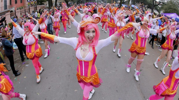 A member of the Pussyfooters dances her way down St. Charles Avenue during a Mardi Gras parade in New Orleans, Louisiana.