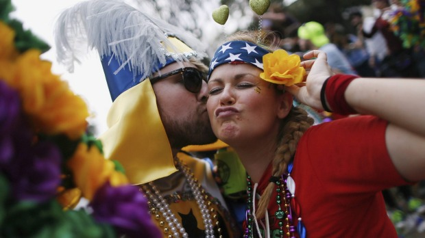Revellers party on St. Charles Avenue during a Mardi Gras parade in New Orleans, Louisiana.