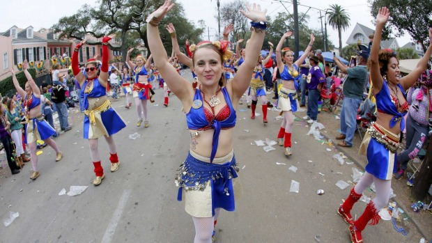 A member of the Organ Grinders dances her way down St. Charles Avenue during a Mardi Gras parade in New Orleans, Louisiana.