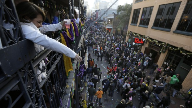 Gina Giacona of New Orleans throws beads from the balcony of the Royal Sonesta Hotel during Mardi Gras day festivities ...