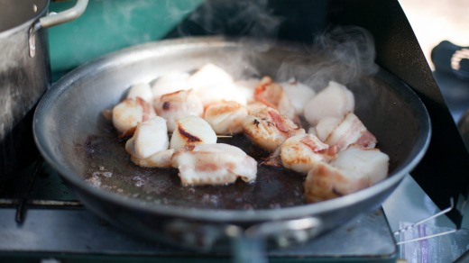 Scallops and bacon for an entree sizzle in a pan.