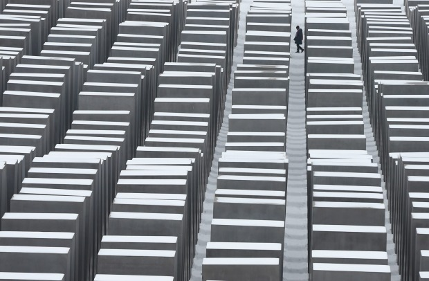 A visitor walks among snow-covered stellae at the Memorial to the Murdered Jews of Europe, also known as the Holocaust ...