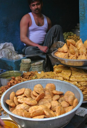 A samosa vendor sells his tasty treats in back alley near a busy Delhi market.