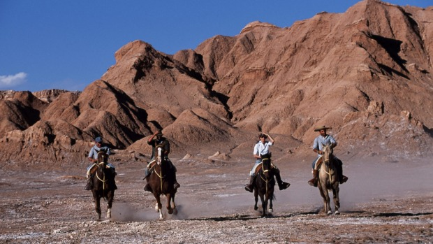 Tourists horse-riding among the wind-eroded peaks and lunar landscape of Moon Valley.