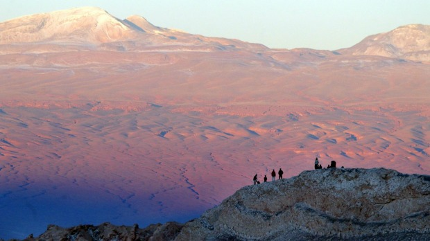 Tourists rest above a hill in Valle de la Luna (Moon Valley) in the nature reserve of Los Flamencos in the Atacama Desert.