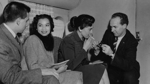 Passengers enjoy a relaxing smoke on a Transocean Air lines Boeing 377 Stratocruiser in the mid 1950's. Transocean Air ...