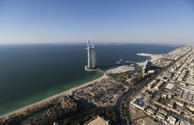 The Burj Al Arab luxury hotel, center, stands offshore near the Jumeirah Beach hotel, right, on the waterfront in Dubai, ...