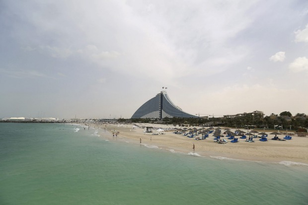 Holidaymakers occupy the beach near the Jumeirah Beach hotel in Dubai, United Arab Emirates.