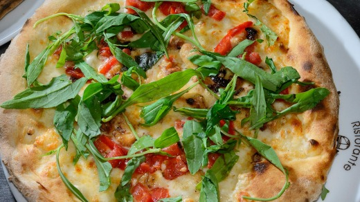 Homemade pizza with tomatoes and rocket