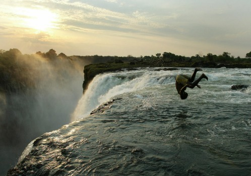 A Zambian man somersaults into a pool at the edge of the 110-metre high main falls of the Victoria Falls on the Zambezi ...