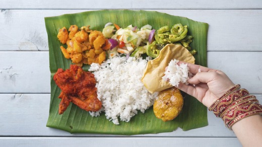 Indian woman eating banana leaf rice.