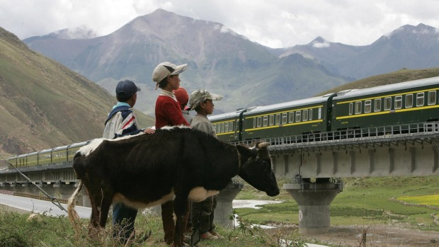 A Train from Lhasa Railway Station travels on the Tibetan grasslands near Lhasa, Tibet.