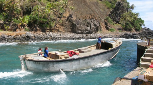 Pitcairn Islanders launch a longboat from Bounty Bay to meet a supply ship anchored offshore.