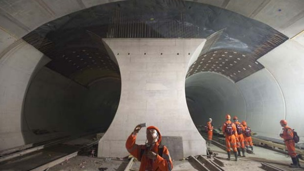 A journalist takes a picture of the 57kms railway tunnel under construction in the Alps at Sedrun.