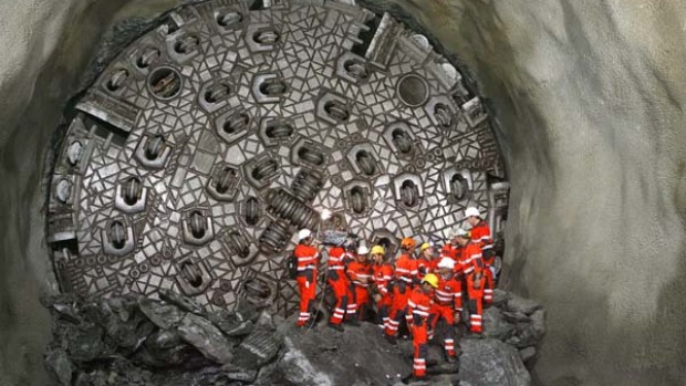 "Miners stand in front of the ""gaby"" drill digging the world's longest tunnel."