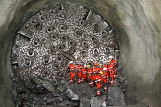 """THE LONGEST RAILWAY TUNNEL IN THE WORLD:  Miners stand in front of the """"gaby"""" drill digging the world's longest tunnel."""