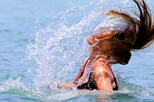 Woman tosses back her wet hair while bathing in Muri Lagoon.