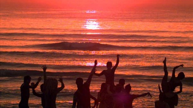 Fresh ... beachgoers dance as the sun rises over Hainan Island.