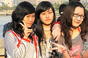 Shanghai. Group of girls being photographed in front of Pudong.