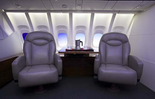 The 747-8 Intercontinental's cabin, featuring larger windows and new lighting, is displayed in a mock up of seats and a ...