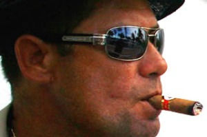 Smokin' ... (left) a Cuban-American rolls a cigar in Miami's art deco district;