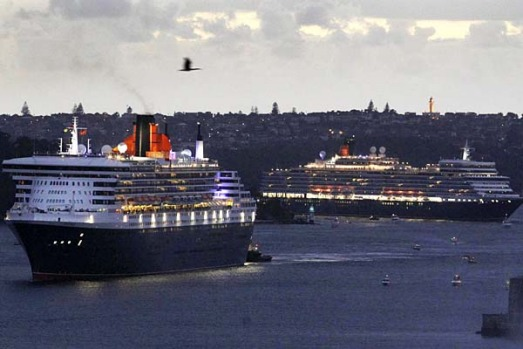 Cruise liners Queen Mary 2, left, and the Queen Elizabeth travel through Sydney Harbour