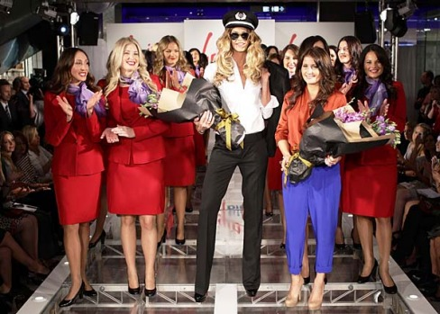 Elle Macpherson and designer Juli Grbac pose with Virgin Blue staff at the launch of Virgin Blue's designer uniforms.