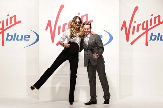Elle Macpherson hugs MC Nick Smith at the launch of Virgin Blue's new designer uniforms.