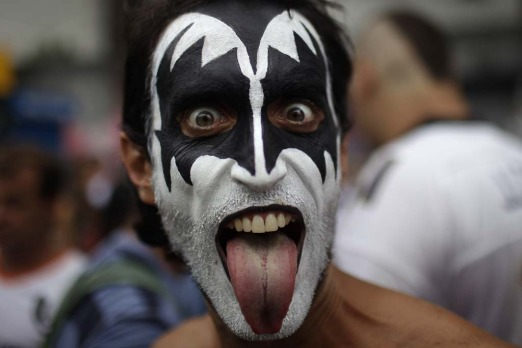A reveller, with his face painted as musical group Kiss member Gene Simmons, sticks his tongue out during the ...