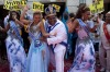 This year's King Momo, the crowned and costumed Milton Rodrigues, centre, flanked by the Carnival queen and two ...
