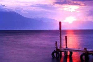 Sun setting on Lake Atitlan, with stream of red sunlight reflected on water surface.
