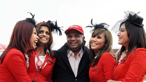 AirAsia chief executive Tony Fernandes (C) with flight attendants.