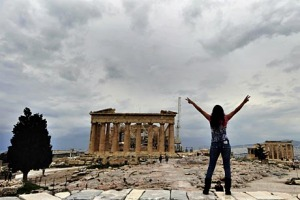 A tourist poses for a photo atop the Acropolis hill with the ancient Parthenon temple in the background,