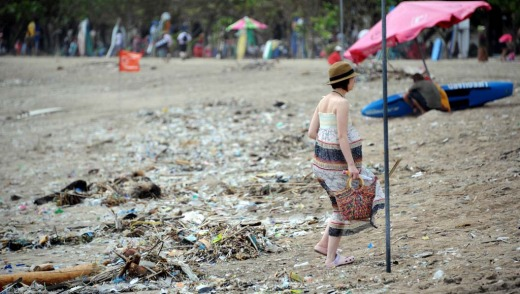 A foreign tourist  walks past debris and rubbish at  Kuta beach.