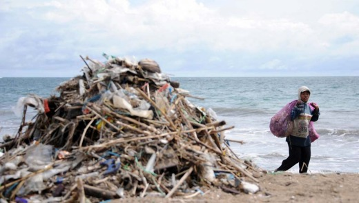 A rubbish collector walks past a pile of garbage on Kuta beach.