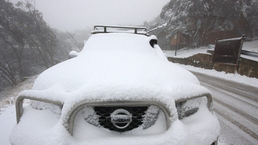 A four-wheel-drive covered with snow after an overnight dump at Mount Buller.
