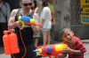 Thai children and foreign tourists spray water on each other on Khaosan road.