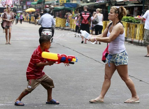 A tourist participates in a water fight with a Thai boy during the Songkran Festival celebration at Khaosan road in Bangkok.