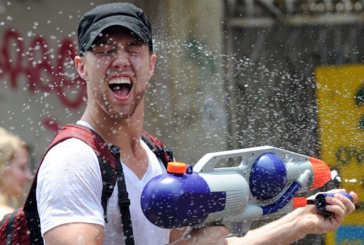 Thai children and foreign tourists spray water on each other on  Khaosan road during Songkran festival in Bangkok .