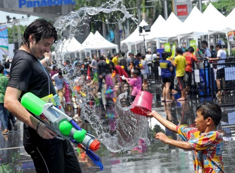 A foreign tourist is splashed with water by a young boy as people come out to mark the start of the Songkran festival, ...