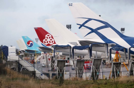 The tailfins of various wide body Boeing aircraft sit aligned and idle at Paine Field in Everett.