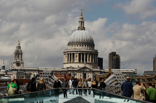 Pedestrians walk across the Millenium Bridge in front of St Paul's Cathedral in London.