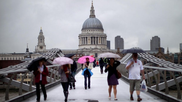 People cross the Millennium Bridge in wet weather in front of the newly restored St Paul's Cathedral.