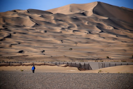 Dunes rise above the Mogao Caves, near Dunhuang, China. Photo: Conrad Walters.