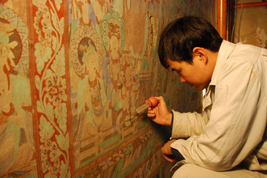 A conservator works to preserve a deteriorated mural in the Mogao Caves. Photo: Conrad Walters.