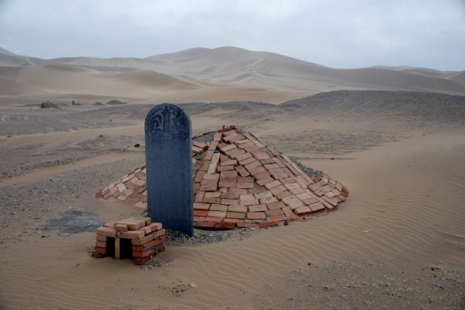 Lonely graves sit on the edge of the dunes outside Dunhuang. Photo: Conrad Walters.