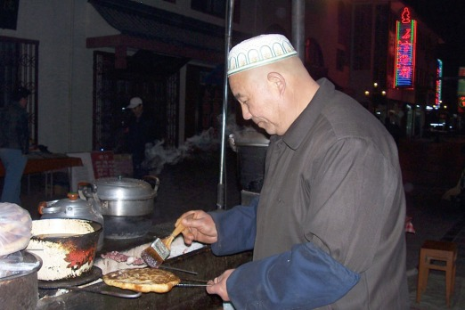 A Muslim hawker prepares bread in Dunhuang's night market. Photo: Joyce Morgan.