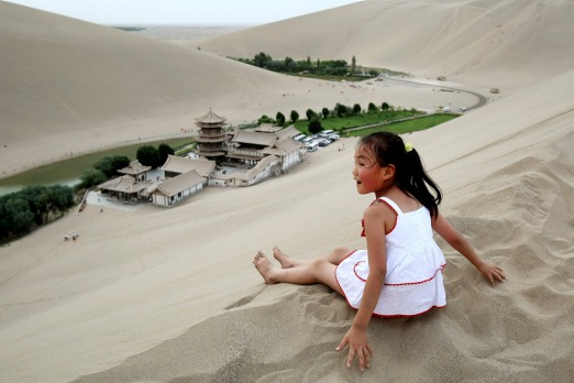 A girl sits atop the Singing Dunes of Crescent Lake, near Dunhuang. Photo: Getty Images/Feng Li.