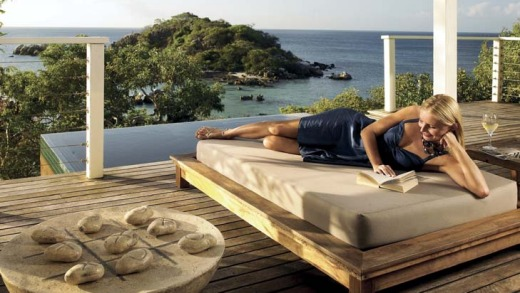 A daybed with views on a villa deck.