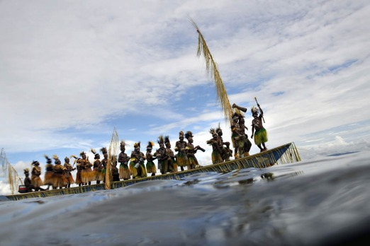 Papuan tribesmen riding a ceremonial boat during the Lake Sentani festival.
